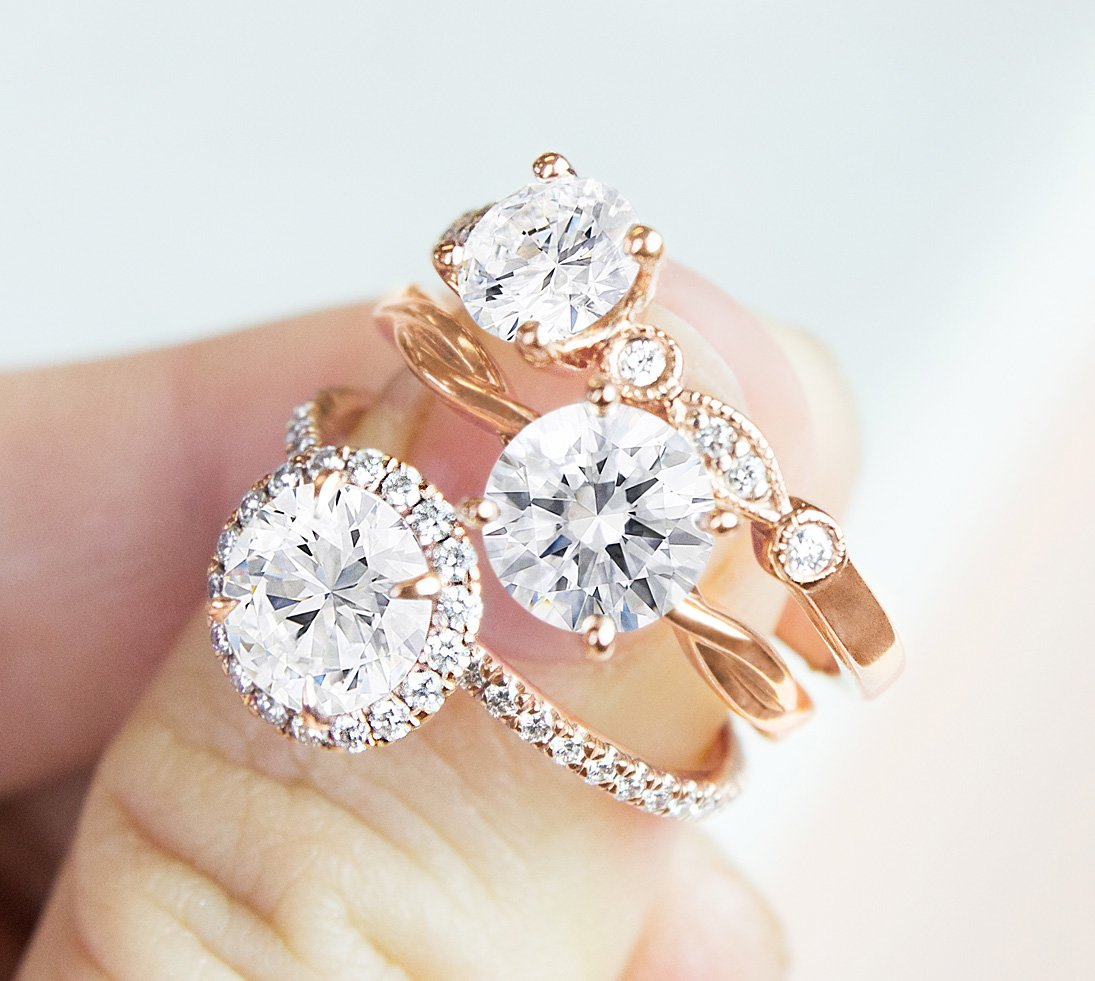 Woman's hand holding three rose gold diamond engagement rings.