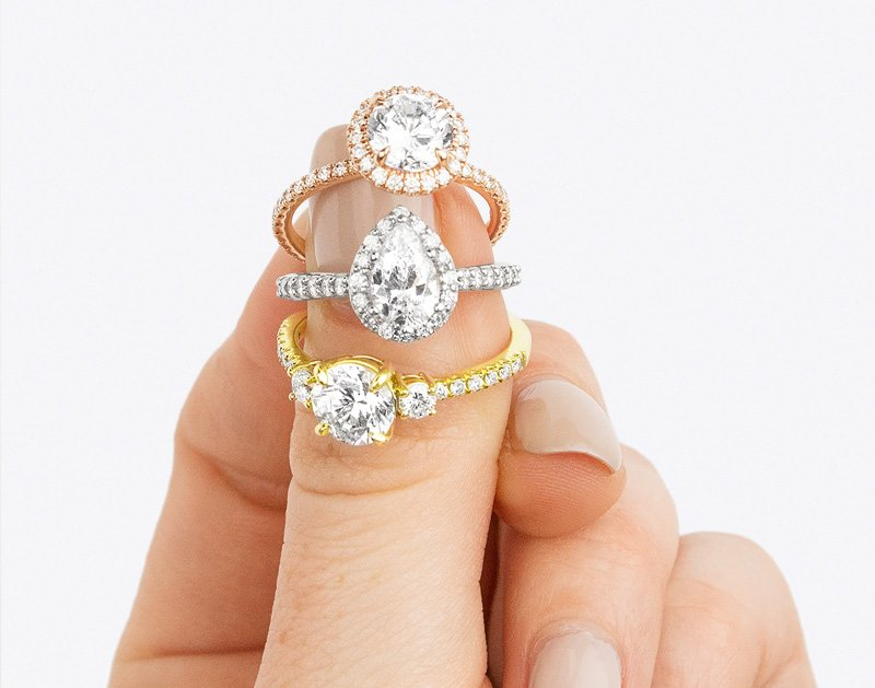 Three engagement rings with various diamond shapes set in rose gold, white gold, and yellow gold.
