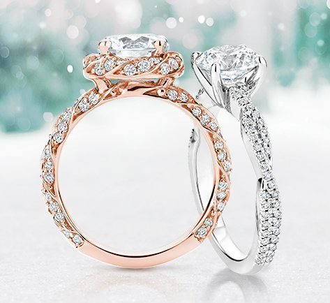 A white gold and rose gold engagement ring leaning on each other
