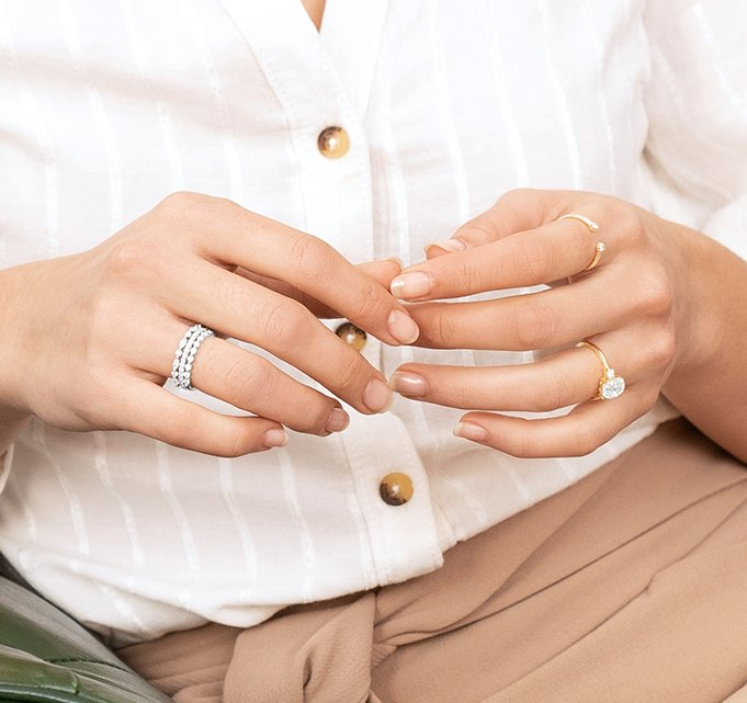 Woman wearing rose gold oval engagement ring and diamond wedding rings