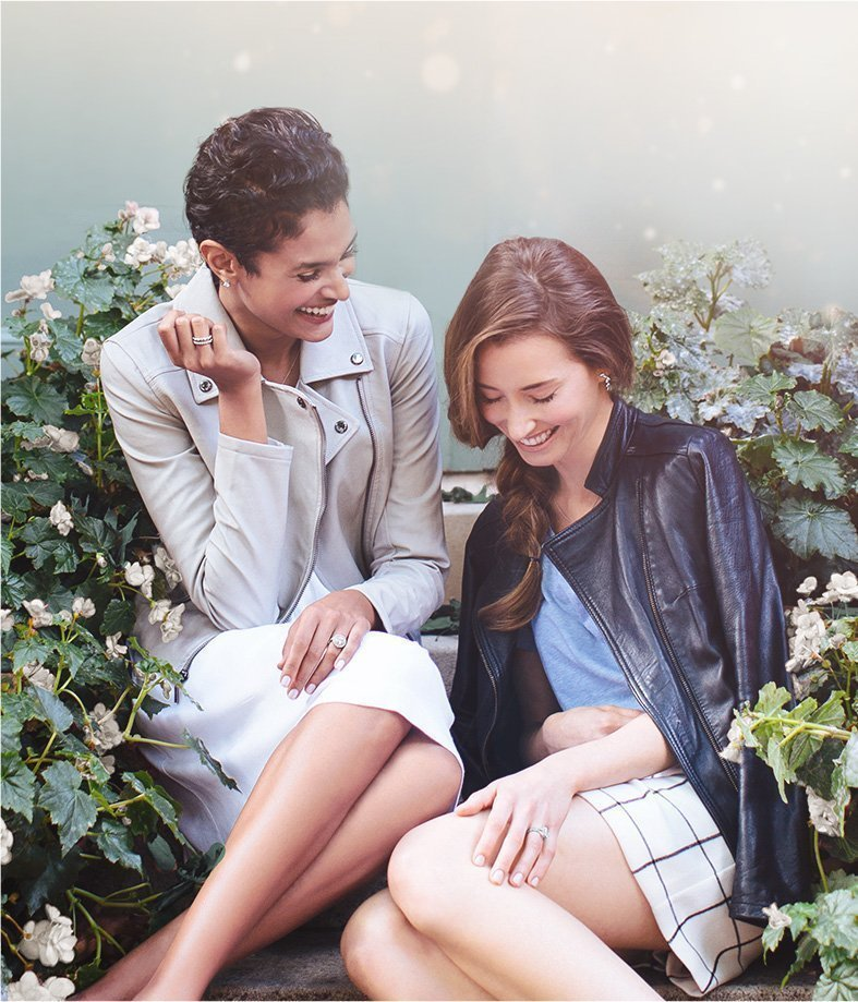 Two women laughing on a park bench wearing engagement rings